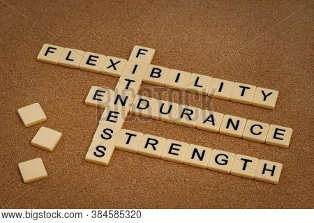 endurance, flexibility, strength - fitness training goals concept, crossword with ivory letter blocks on cork bulleting board