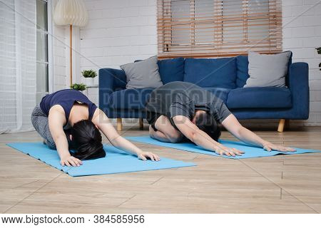Asian Couples Exercise Together At Home In The Living Room. To Maintain Good Health And Social Dista