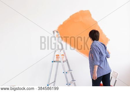 Middle-aged Woman Painting The Walls Of New Home. Renovation, Repair And Redecoration Concept. Copy