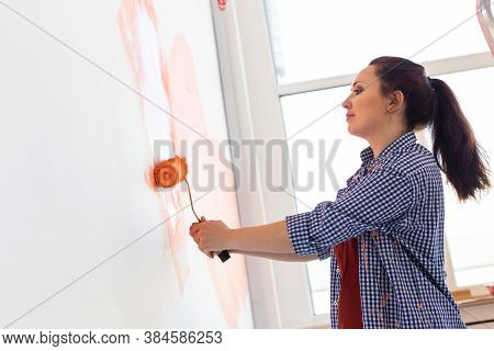 Happy Smiling Woman Painting Interior Wall Of New House. Redecoration, Renovation, Apartment Repair