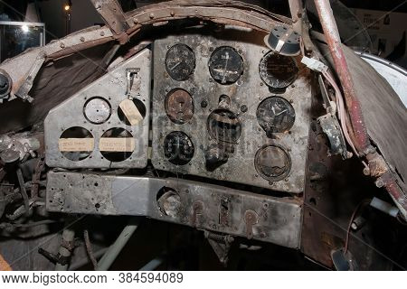 Remains Of The Cockpit Of A Crashed World War Two Fighter With Broken Gauges. Labels Tell Which Gaug