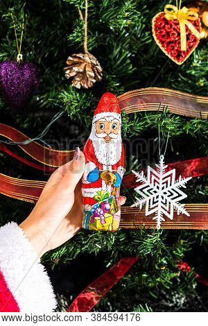 Hand Holding Santa Claus Chocolate Figurine In Front Of The Christmas Tree. Decorating Christmass Tr