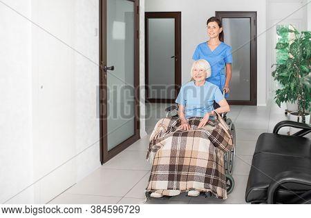 Friendly Geriatric Nurse Assisting Senior Woman In A Wheelchair At Nursing Home Corridor, Caring For