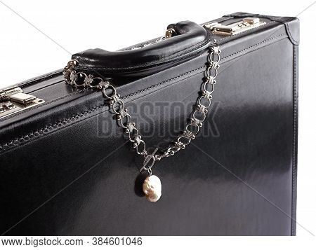 Silver Chain Necklace With Baroque Pearl Pendant On Male Black Leather Briefcase. Close-up Shot