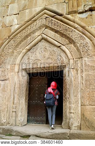 Female Traveler In Head Covering At The Entrance To The Church Of The Assumption In Ananuri Fort, Ar