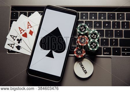 Poker Chips, Cards And Smartphone On A Laptop Keyboard. Poker Online Concept