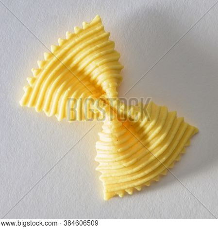 Colored Bow Tie Pasta. Closeup Single Yelow Farfalle On Gray Background.