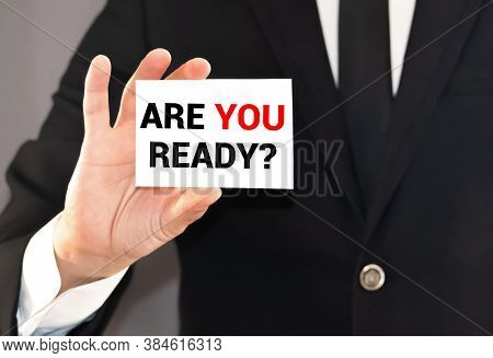 Man Holding A Card With The Text Are You Ready. On A Beach Background.