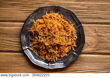 Indian Pilaf With Biryani Rice On Wooden Rustic Background. Traditional Indian Dish Pilaf With Meat
