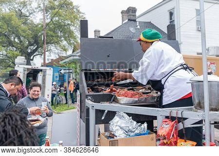 New Orleans, Louisiana/usa - 3/17/19: Woman Cooking Meat On Grill Outdoors In Central City Neighborh