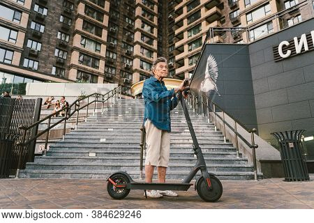 Active Old Woman Riding Electric Scooter. Retired Lady Uses Environmentally Friendly City Vehicle. G