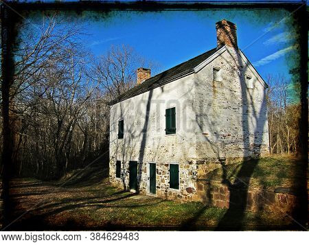 An Abandoned Stone Lock House Sits Barren In The Woods Along The C&o Canal Towpath And The Potomac R