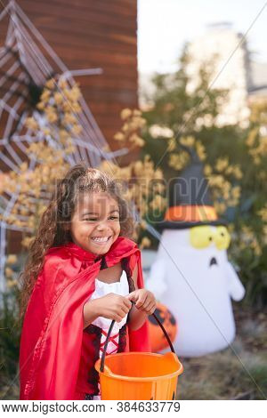 Girl Wearing Fancy Dress Outside House Collecting Candy For Trick Or Treat