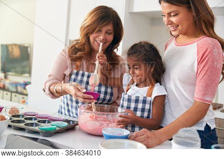 Multi-Generation Hispanic Female Family Having Fun In Kitchen At Making Cake Together