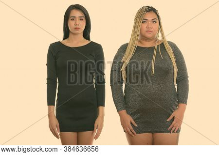 Studio Shot Of Young Asian Transgender Woman And Fat Asian Woman Standing Together