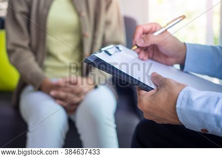 The Doctor Or Psychiatrist Holds A Clipboard To Record The Mental Illness Of Female Patients. Therap