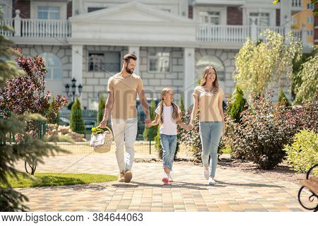Young Cute Family Walking Vigorously And Looking Happy