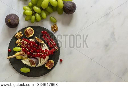 Oven Baked Camembert Cheese With Honey, Fruits, Nuts, And Berries On A Marble Background. Top View,