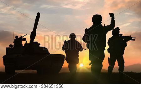 Soldiers And Tank On Battlefield At Sunset