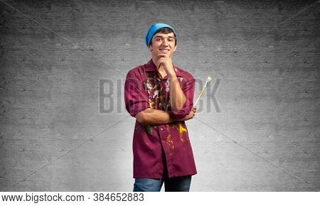 Pensive Painter Artist Standing With Folded Arms On Gray Wall Background. Portrait Of Young Man Look