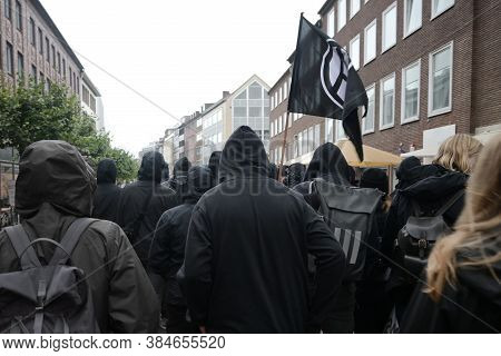 Black Dressed Protesters On A Demonstration March Through The Streets Of Lubeck Against German Polit
