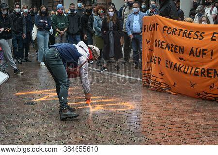 Lubeck, Germany, September 09, 2020: Demonstrator Sprays A Slogan On The Street On The Demonstration