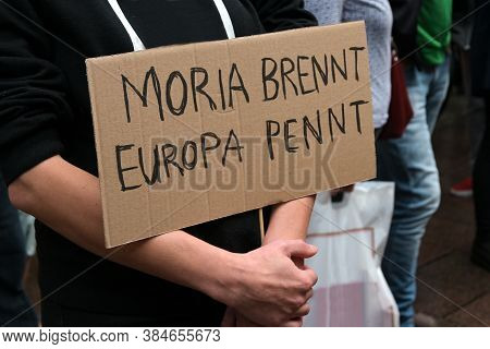 Demonstrator Holds A Cardboard Sign With German Text Moria Brennt, Europa Pennt, Meaning Moria Is Bu
