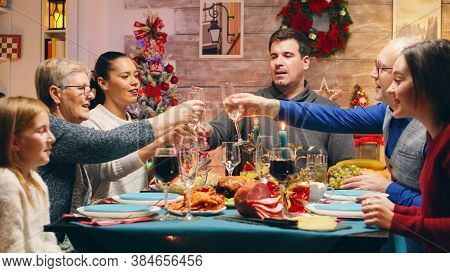 Family With Different Ages Clinking Glasses With Champagne Celebrating Christmas. Traditional Festiv