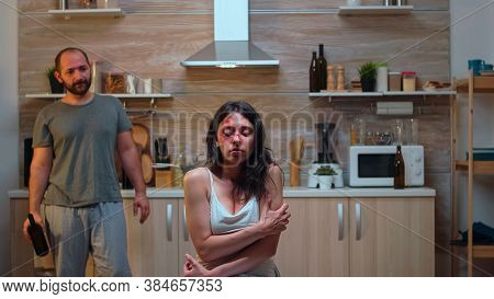 Alcoholic Man Threating Scared Woman In The Kitchen. Abused Terrified Beaten Wife Covered In Bruises