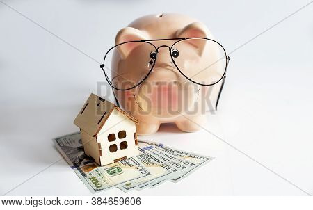 Piggybank With Wooden House And Dollars. Isolated On White Background