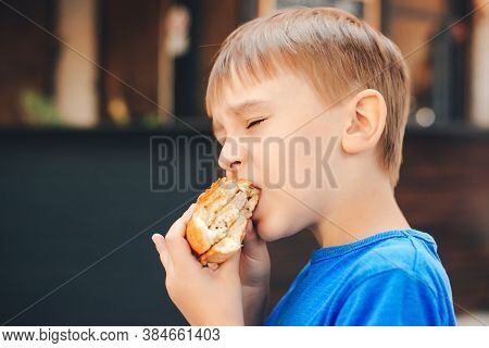 Hungry Kid Eating A Burger At Outdoors Cafe. Cute Child Eating Fast Food. Childhood, Unhealthy Food