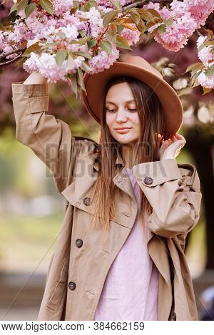 Beautiful Young Brunette Woman With Long Hair Flying In The Wind And Brown Hat In A Flowering Garden