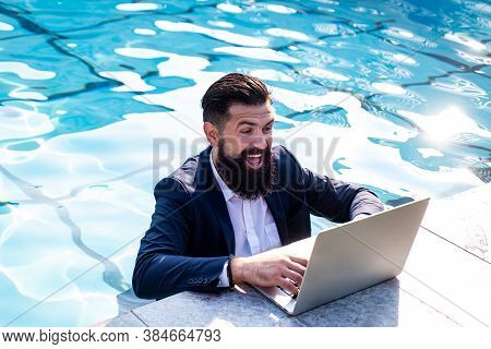 Excited Businessman In Suit With Laptop In Swimming Pool. Funny Business Man, Crazy Comic Business C