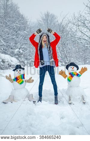 Snowman And Funny Girl The Friend Is Standing In Winter Hat And Scarf With Red Nose. Snowman And Fun