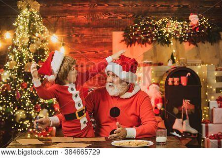 Santa Helper. Kid Grandson And Grandfather In Santa Hat Writing Wish List - Unfocused Lights Backgro