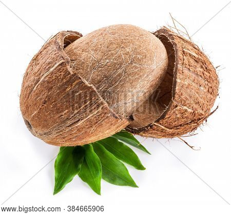 Split coconut fruit with whole inside seed over green leaves isolated on white background.