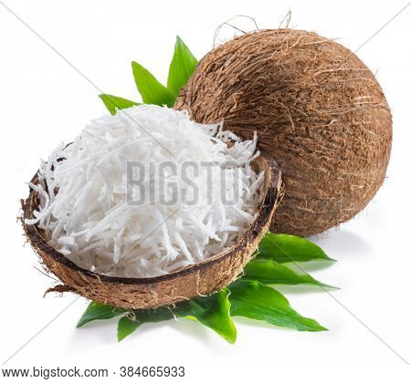 Cracked coconut fruit with white shredded flesh and whole coconut isolated on white background.
