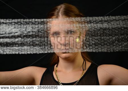 Beautiful Young Woman Face Close Up Portrait In Studio On Black. Bubble Wrap