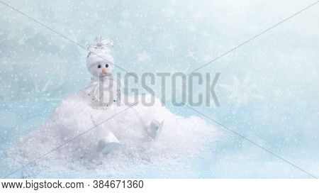 Christmas Festive Background. Xmas Greeting Card. Christmas Toy Cute Small Snowman Is Sitting On Whi