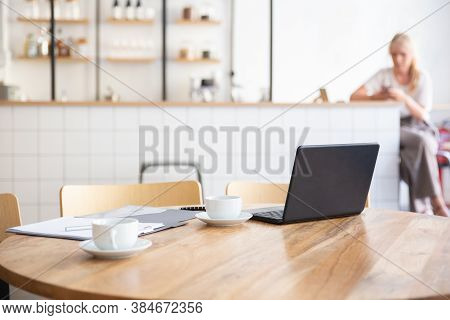 Empty Workplace In Co-working Space. Round Table With Laptop, Coffee Cups And Documents On It. Young