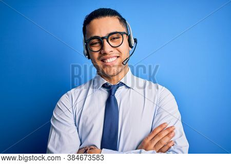 Young brazilian call center agent man wearing glasses and tie working using headset happy face smiling with crossed arms looking at the camera. Positive person.