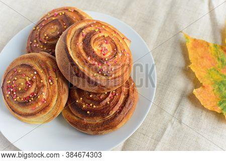 Fresh Baked Cinnamon Rolls Or Buns With Sugar Sprinkle Topping On White Plate And Autumn Leaf On Tab