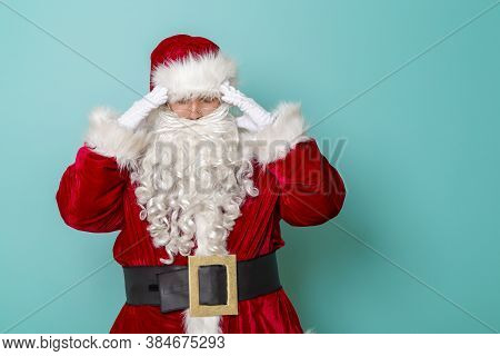 Santa Claus Holding Head In Hands, Having A Headache, Isolated On Mint Colored Background; Santa Cla