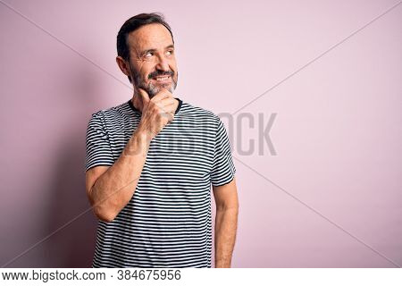 Middle age hoary man wearing casual striped t-shirt standing over isolated pink background with hand on chin thinking about question, pensive expression. Smiling with thoughtful face. Doubt concept.