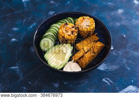 Healthy Plant-based Food Recipes Concept, Nourish Bowl With Avocado Cucumber Polenta Chips And Spicy