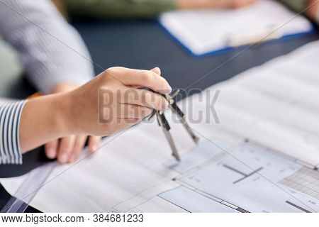 construction business, architecture and building concept - close up of architect with blueprint and drafting compass working at office