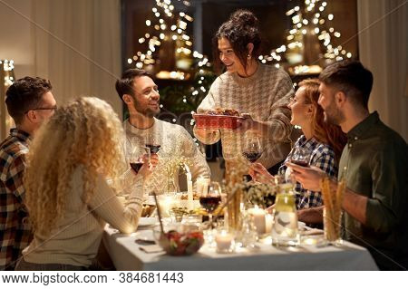 holidays, celebration and people concept - happy smiling friends having christmas dinner at home in evening