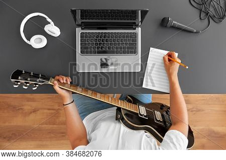 leisure and people concept - young man or musician with laptop computer and guitar writing to music book at table