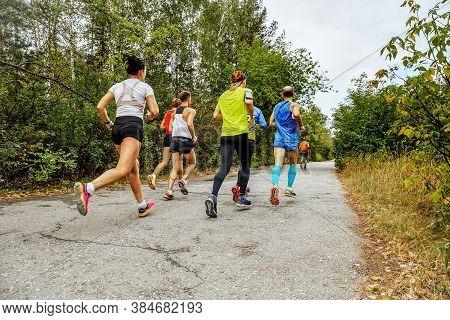 Group Runners Women And Men Run Race On Road Autumn Park