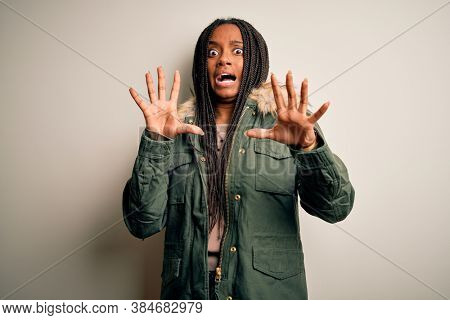 Young african american woman wearing winter parka coat over isolated background afraid and terrified with fear expression stop gesture with hands, shouting in shock. Panic concept.